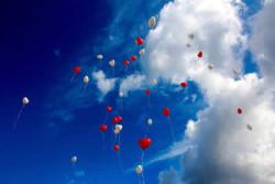 Herzluftballons im blauen Himmel