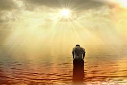 Mann gebeugt im Meer bei Sonnenlicht
