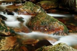 Wasser, das nebelig über Steine fließt
