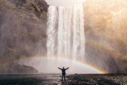 fülle-gesetz-der-anziehung-the-secret-freigeist-mensch-am-fuss-eines-wasserfall-mit-asugebreiteten-Armen-waterfall