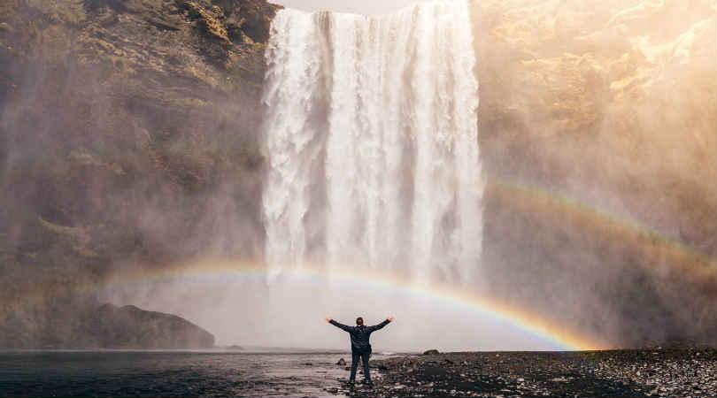 freigeist-mensch-am-fuss-eines-wasserfall-mit-asugebreiteten-Armen-waterfall