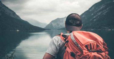 mann-mit-rucksack-am-see-auf-selbstfindungs-reise