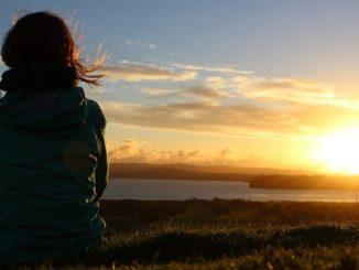 Frau sitzt in der Abendsonne am See
