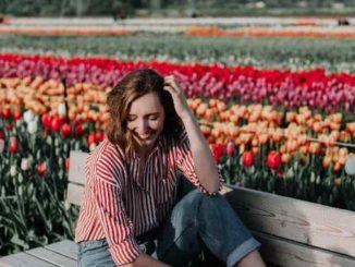 Frau sitzt lächeln auf einer Bank umgeben von einem Blumenmeer