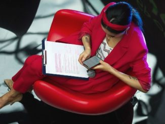 frau mit unterlagen und handy im roten stuhl