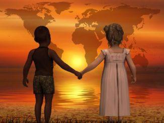 kinder-stehen-in-der-Abendsonne-in-Verbundenheit-Hand-in-Hand-am-Ufer-und-schauen-in-Liebe-auf-die-Welt