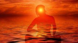 meditative silhouette einer frau im abendrot im meer